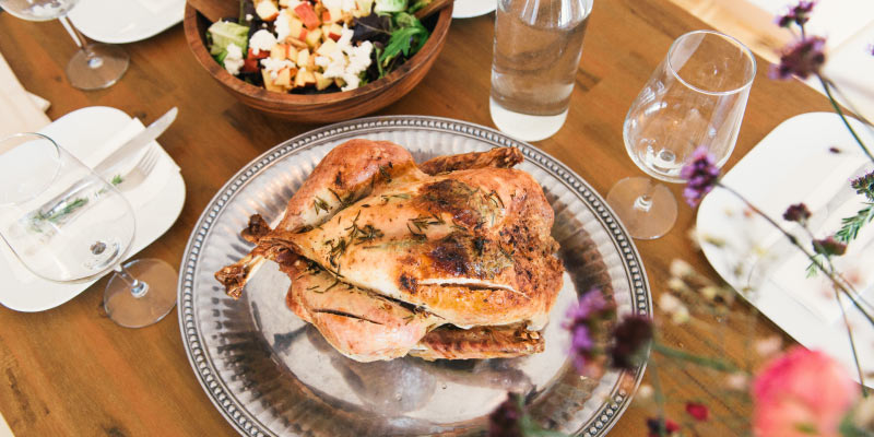 Aerial view of a Thanksgiving turkey on a silver platter next to  water glasses and a salad